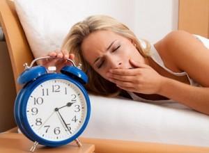 Schlaflos mit Uhr in der Nacht. Frau kann nicht schlafen.